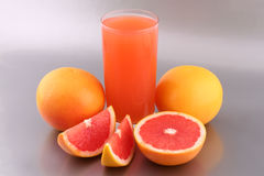 Grapefruit juice. And ripe grapefruits on silver background stock image