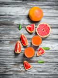 Grapefruit juice in a glass and pieces of fresh grapefruit royalty free stock photos