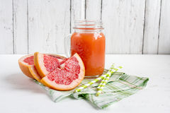 Grapefruit juice in a jar. Grapefruit on a white wooden background. Selective focus Royalty Free Stock Photo