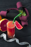 Grapefruit juice, measuring tape and dumbbells Royalty Free Stock Photos