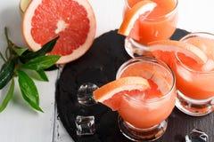 Grapefruit juice and ripe grapefruits stock images