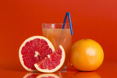 Grapefruit juice. Whole red grapefruit, cross section and a slice placed next to a glass of grapefruit juice with drinking straw isolated on red background Stock Photography