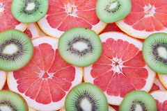 Grapefruit and kiwi rings as background Royalty Free Stock Photo