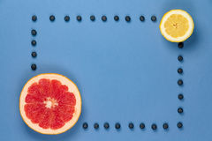 Grapefruit and lemon with frame of blueberries Royalty Free Stock Photography