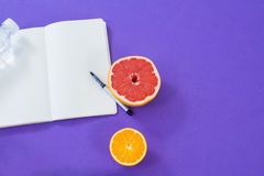 Grapefruit, lemon with opened book and pen Stock Photos