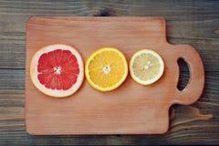 Grapefruit lemon orange on a dark background. Fresh citrus on color wooden background Royalty Free Stock Photography