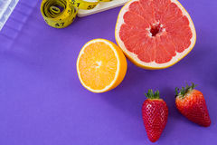 Grapefruit, lemon, strawberry with measuring tape Royalty Free Stock Photo
