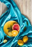 Citrus slices with tablecloth. Grapefruit, lime and orange slices on plate with tablecloth on wooden tabletop Royalty Free Stock Photos