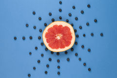 Grapefruit looks like a sun with rays of blueberries Stock Images
