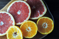 Grapefruit and Mandarin on a wooden Board stock images