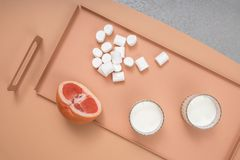 Grapefruit, marshmallows and glasses with milk Royalty Free Stock Photos