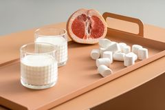 Grapefruit, marshmallows and glasses with milk Stock Image