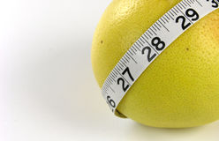 Grapefruit Measuring Tape. A measuring tape around a grapefruit. Remember the grapefruit diet. Great for the concepts of health, weight, waistline, diet Royalty Free Stock Images