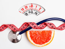 Grapefruit with measuring tape on weight scale. Dieting Royalty Free Stock Photography