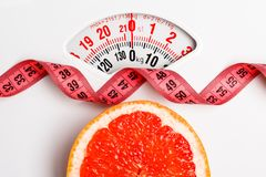 Grapefruit with measuring tape on weight scale. Dieting Stock Images
