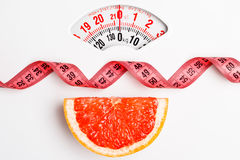 Grapefruit with measuring tape on weight scale. Dieting Royalty Free Stock Images