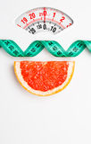 Grapefruit with measuring tape on weight scale. Dieting Stock Photo
