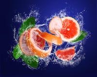 Grapefruit met stukken en bladeren in waterdalingen Royalty-vrije Stock Foto