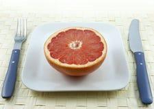 Grapefruit met vork en mes royalty-vrije stock foto's