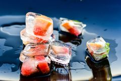 Ice cubes. Grapefruit and mint frozen in ice cubes on black background with reflection. Luxurious fresh summer fruit eating. Wallpaper royalty free stock image