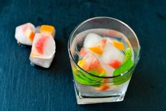 Fruit in ice cubes in water. Grapefruit and mint frozen in ice cubes in water  on black background . Luxurious fresh summer fruit eating. Detox drink Royalty Free Stock Photography
