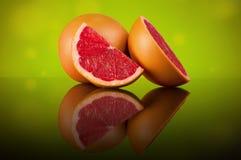 Grapefruit op een heldere abstracte achtergrond met bezinning Stock Foto