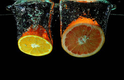 Grapefruit and orange falling into water. Red grapefruit and orange falling into water royalty free stock image
