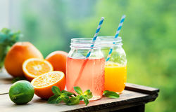 Grapefruit and orange juice in glass jars in the open air. Stock Photos