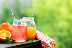 Grapefruit and orange juice in glass jars in the open air. Royalty Free Stock Photography