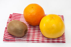 Grapefruit, orange and kiwi on a dish towel Royalty Free Stock Image