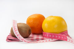 Grapefruit, orange and kiwi with tape measure Stock Image