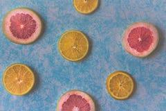 Grapefruit and orange slices on light blue background photograph. Photograph of some grapefruit slices on light blue background Royalty Free Stock Image