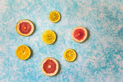 Grapefruit and orange slices on light blue background photograph. Photograph of some grapefruit slices on light blue background Stock Photography
