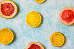 Grapefruit and orange slices photograph. Photograph of some grapefruit slices on light blue background Royalty Free Stock Images