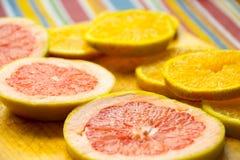 Grapefruit and orange slices on wood cutting board photograph. Photograph of some grapefruit and orange slices on wood cutting board Royalty Free Stock Images