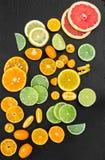 Grapefruit, orange, tangerine, lemon, lime and kumquat on black Stock Photos