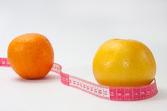 Grapefruit and orange with tape measure Royalty Free Stock Images