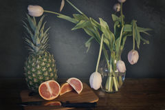 Grapefruit. Pineapple, grapefruit, tulips and background Royalty Free Stock Images