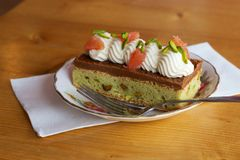 Grapefruit-pistachio pastry with cream on plate with fork. A view of a gourmet pastry topped with pistachios, cream and grapefruit segments. The pastry is served Royalty Free Stock Photography