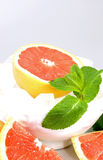 Grapefruit on the rocks. Grapefruit half in a white bowl on ice cubes decorated with fresh mint leaves and grapefruit quarters Stock Photo