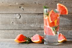 Grapefruit, rosemary detox water against a rustic wood background Stock Photos