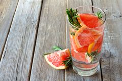 Grapefruit, rosemary detox water downward view on rustic wood Royalty Free Stock Photos