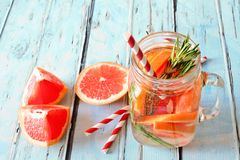 Grapefruit, rosemary detox water in a jar over blue wood Stock Image