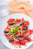 Grapefruit salad with olives, red onion, basil. On the table Stock Photo