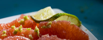Grapefruit sections with lime zest on a white plate. And a blue background Stock Photo