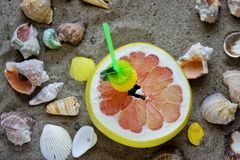 A grapefruit with shells on the sand, a cocktail of exotic fruits and natural juice, a tube for cocktails. A grapefruit with shells on the sand, a cocktail of stock photography