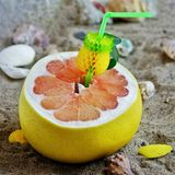 A grapefruit with shells on the sand, a cocktail of exotic fruits and natural juice, a tube for cocktails. A grapefruit with shells on the sand, a cocktail of stock images