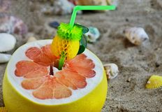 A grapefruit with shells on the sand, a cocktail of exotic fruits and natural juice, a tube for cocktails. A grapefruit with shells on the sand, a cocktail of royalty free stock image