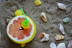 A grapefruit with shells on the sand, a cocktail of exotic fruits and natural juice, a tube for cocktails. A grapefruit with shells on the sand, a cocktail of royalty free stock photography