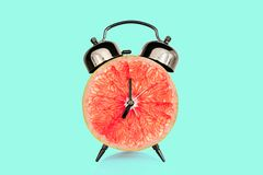 Grapefruit slice on alarm clock, blue pastel background. fruit and vitamins diet nutrition concept stock photography